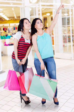 spending full: Portrait of happy women carrying shopping bags while pointing and looking at store in the shopping center