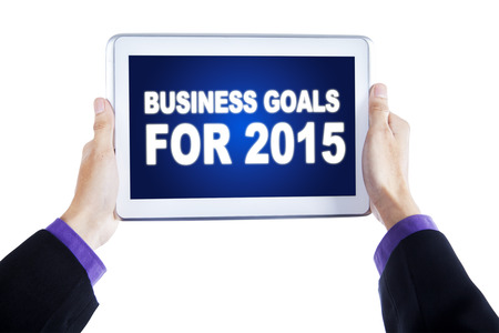 Closeup of worker hands holding a digital tablet with a text of business goals for 2015 on the screen photo