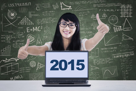 thumbsup: Happy female student sitting in the class and showing thumbs-up with numbers 2015 on the laptop Stock Photo