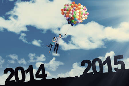 Cheerful couple flying with colorful balloons in the sky above number 2014 to 2015 photo