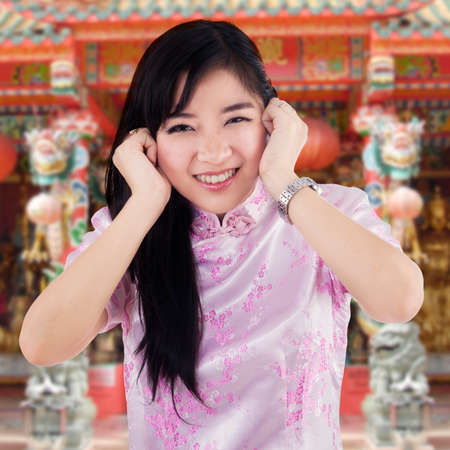 Portrait of cheerful chinese girl wearing cheongsam clothes in the temple photo