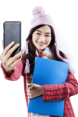 Portrait of teenage student in winter clothes taking self photo with a mobile phone, isolated on white photo