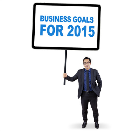 Young male entrepreneur in formal suit, holding a board with a text of business goals for 2015 photo