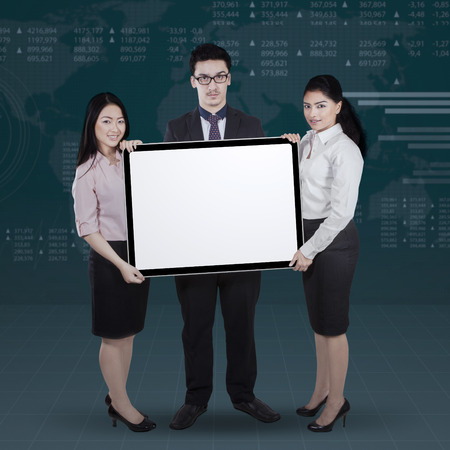 Group of young businesspeople holding empty board with financial background photo