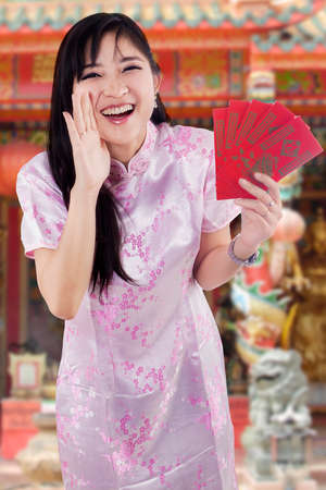 Cheerful chinese girl wearing cheongsam clothes and holding envelope while announcing Happy Chinese New Year in the temple photo
