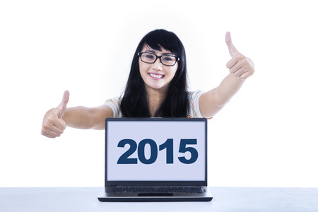 thumbsup: Joyful young girl giving thumbs-up at the camera with numbers 2015 on the laptop, isolated on white