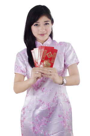 Portrait of young chinese girl in traditional cheongsam dress showing red envelope, isolated on white photo