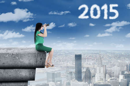 Businesswoman sitting on the roof and using a binocular to look at numbers 2015 at the sky photo
