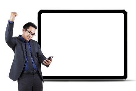 Cheerful businessman celebrate his success while reading good news on cellphone in front of empty board photo