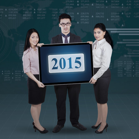 Three members of multiracial businessteam holding number 2015 in front of stock exchange background photo
