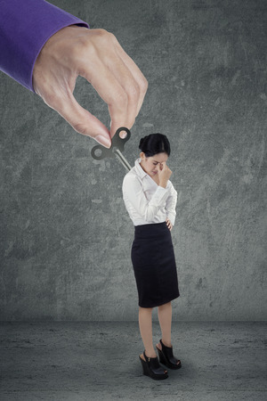 overwork: Young business woman having headache after overwork controlled by hand
