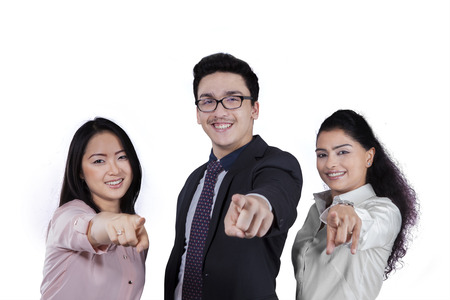 Three members of attractive entrepreneurs smiling and pointing at camera, isolated on white background photo