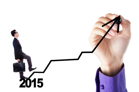 upward graph: Young businessman walking upward on a business graph with number 2015