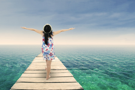 inhale: Asian woman raised her hands on beach deck symbolizing freedom Stock Photo