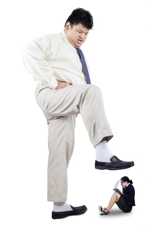 Overweight businessman stepping his foot to crush female worker, isolated on white photo