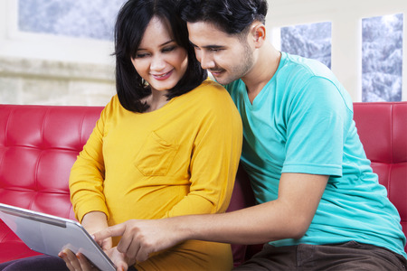 Pregnant woman with her husband using a digital tablet on sofa at home photo