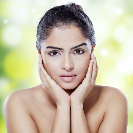 woman in spa: Portrait of female model with gorgeous face and perfect skin looking at camera against bokeh background Stock Photo