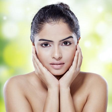 mujer elegante: Retrato de modelo de mujer con la cara hermosa y una piel perfecta mirando a la c�mara contra el fondo bokeh