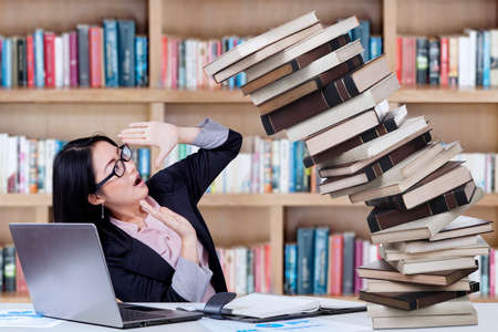 overwork: Young college student in business suit holding on falling books in the library