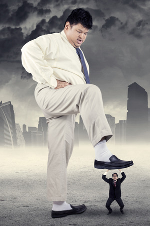 trample: Big businessman try to trample his little employee, symbolizing bossy businessman Stock Photo