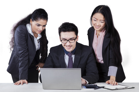 calculator chinese: Caucasian businessman working on laptop computer with two female employees
