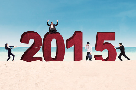 to arrange: Group of business people arrange number 2015 on beach