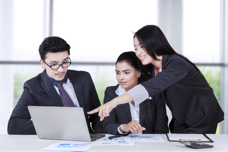Portrait of chinese businesswoman pointing at the laptop and explain documents to her colleague