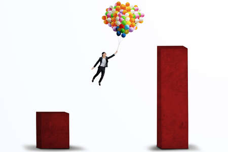 financial obstacle: Young businesswoman flying with balloons over upward business chart to higher chart Stock Photo