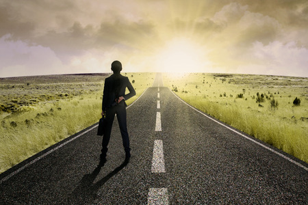 success concept: Businesswoman standing on the highway road, symbolizing as the way to the new opportunity