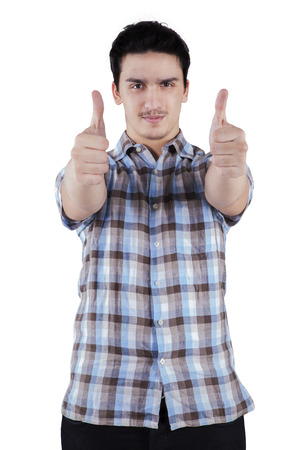 Happy casual young man showing thumb up and smiling, isolated on white background photo
