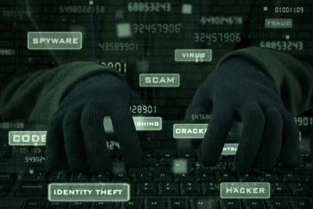 identity protection: Hacker hands wearing gloves typing on keyboard to steal user ID