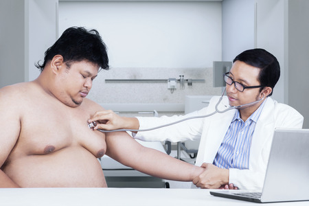 Portrait of male doctor using stethoscope to check overweight patient photo