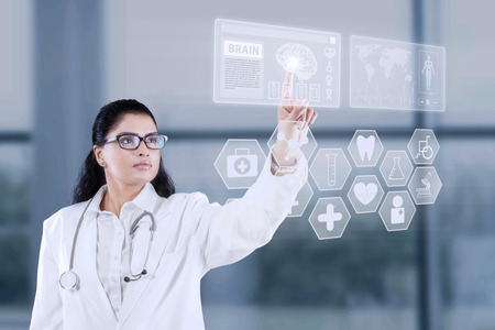 Portrait of female doctor working with futuristic touchscreen interface in the hospital photo