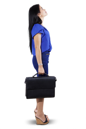 suit case: Full length of businesswoman in blue suit, holding a briefcase while looking at copyspace Stock Photo