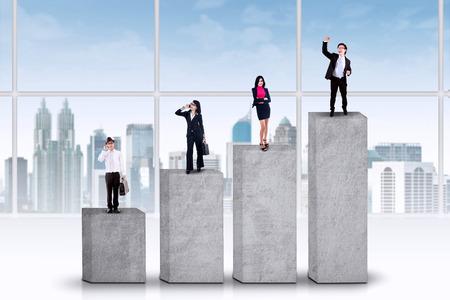 jonge ondernemers: Vier jonge ondernemers die zich op zakelijke grafiek, het symbool van hun prestatie