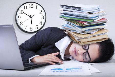 그녀의 머리 위로 서류와 함께 사무실에서 자고있는 인도 기업가의 초상화 스톡 콘텐츠