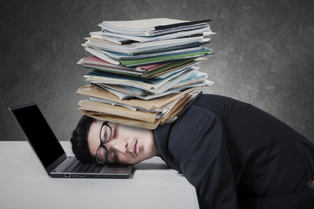 Young businessman sleeping on the laptop computer with documents on his head photo