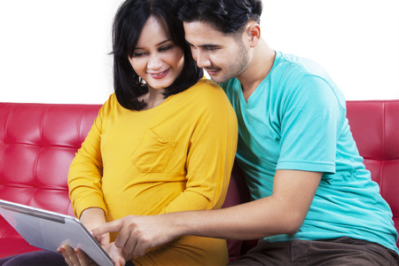 Portrait of happy expectant mother sitting on sofa while using a digital tablet with her husband photo