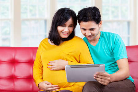 Portrait of young pregnant woman sitting on sofa with her husband while using a digital tablet photo