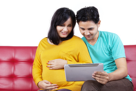 Portrait of happy pregnant woman sitting on sofa while using a digital tablet with her husband photo