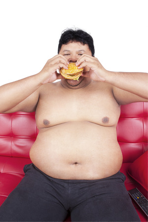 overweight man: Portrait of asian man with fat body sitting on sofa while eating burger Stock Photo
