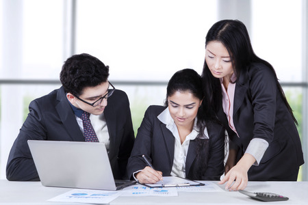calculator chinese: Businesswoman with her partners signing a business document in the office Stock Photo