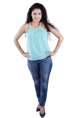Full length of attractive woman with curly hair standing in the studio, isolated on white photo
