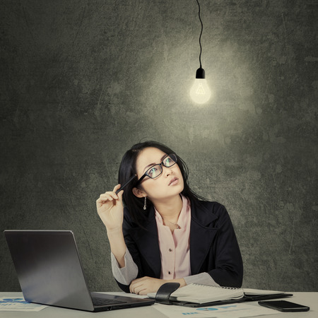 Portrait of young businesswoman with pen thinking solution while looking up at lightbulb photo