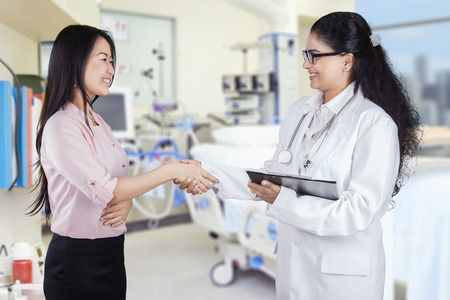 handshaking: Portrait of young doctor shaking hands with chinese patient in the hospital Stock Photo