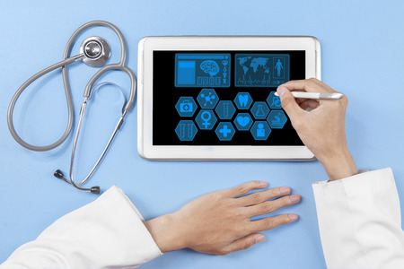 stylus pen: Closeup of physician hands with stethoscope and using a stylus pen to touch tablet screen