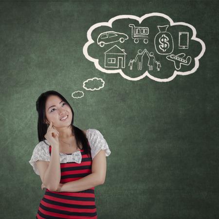 Chica joven pensativa que piensa que su plan de futuro en la clase con nube de etiquetas de su sueño