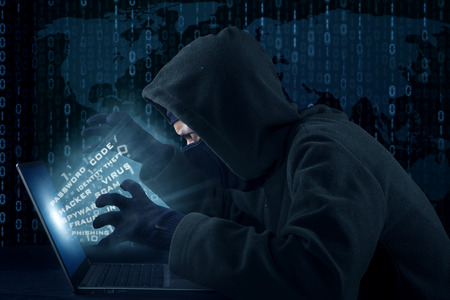 Portrait of male hacker wearing black mask and stealing user identity photo
