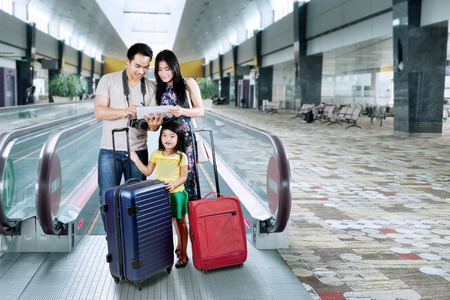 holiday destination: Asian family doing holiday trip and looking a map on the digital tablet at the airport hall