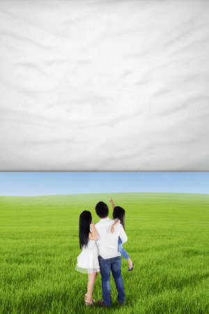 Back view of happy family standing on the meadow while looking at empty banner photo